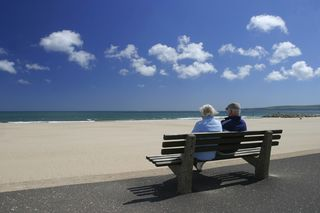 Elderly couple on a bench looking at the ocean