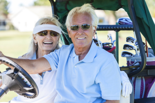 Elderly couple golfing