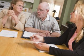 Elderly couple reviewing docs with an agent